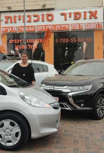 אשה מצולמת ליד הרכב שקנתה באופיר סוכנויות